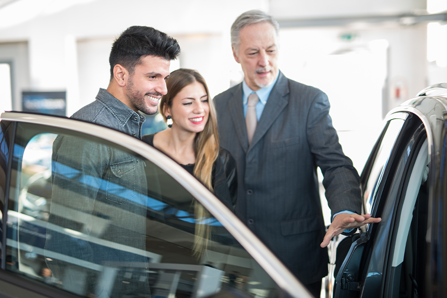 Dealership Insurance - Car Saleman Dealer Showing Car to Young Couple in Showroom