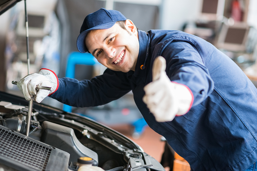 Garage Repair Shop Insurance - Mechanic Giving Thumbs Up to Camera While Working on Vehicle with Hood Open