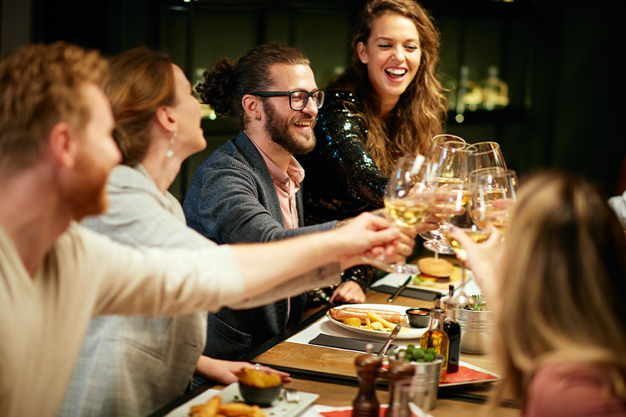 Restaurant Insurance - Friends Sitting in Restaurant for Dinner and Making a Toast with White Wine