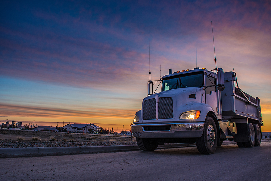 Trucking Insurance - Truck Driving on Road at Dusk