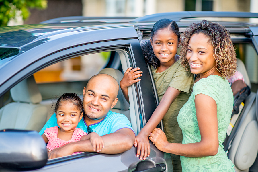 Auto Insurance - Portrait of Family Posing and Getting into Vehicle With Dad and Daughter in Front Seat and Mom and Daughter Standing With Door Open