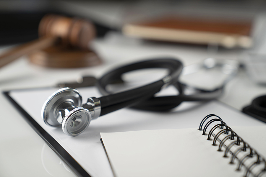 Medical Malpractice Insurance - Medical Law Concept with Gavel, Notebook and Stethoscope on a White Table
